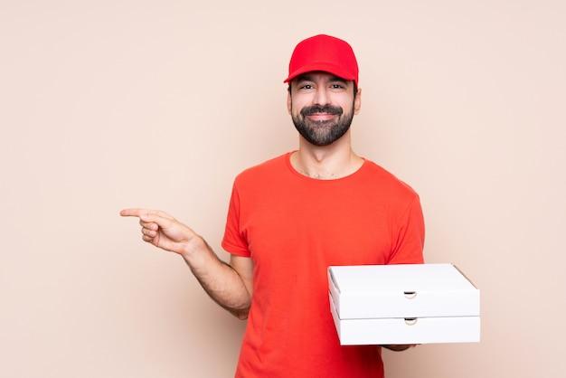 Jovem, segurando uma pizza apontando o dedo para o lado