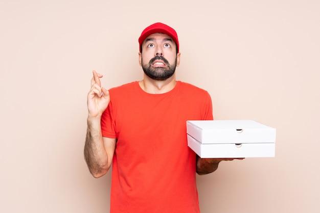 Jovem, segurando uma pizza com dedos cruzando e desejando o melhor