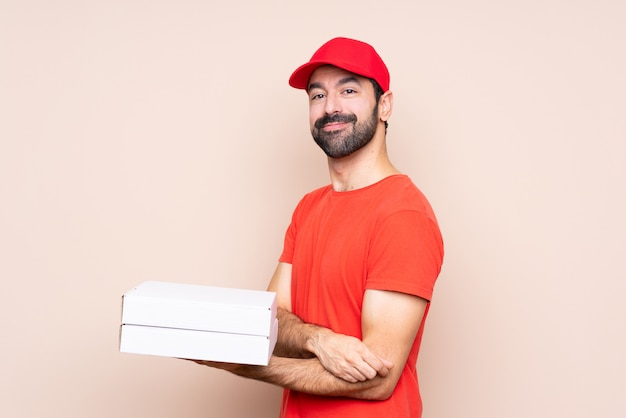 Jovem, segurando uma pizza com os braços cruzados e olhando para a frente