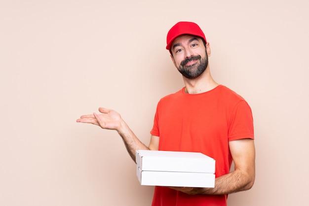 Jovem, segurando uma pizza, estendendo as mãos para o lado para convidar para vir