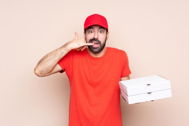 Jovem, segurando uma pizza, fazendo gesto de telefone e duvidando
