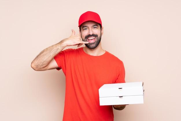 Jovem, segurando uma pizza fazendo gesto de telefone. ligue para mim de volta
