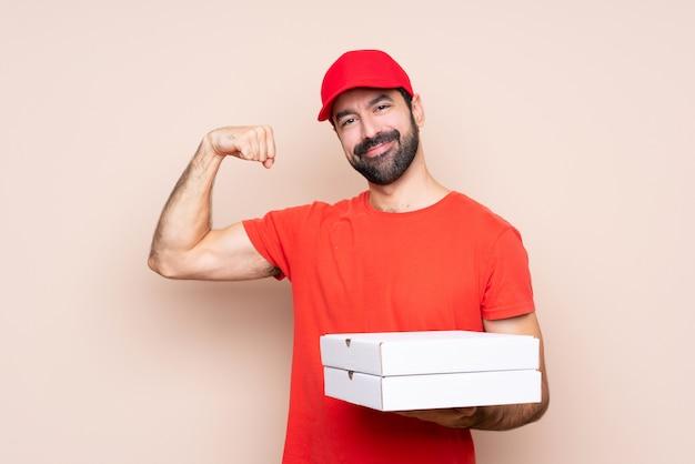 Jovem, segurando uma pizza, fazendo um gesto forte