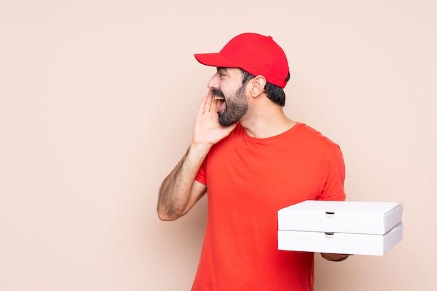 Jovem, segurando uma pizza gritando com a boca aberta para a lateral