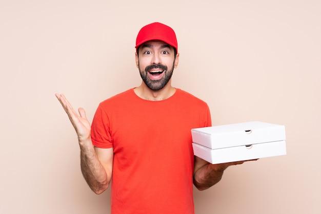 Jovem, segurando uma pizza isolado com expressão facial chocado
