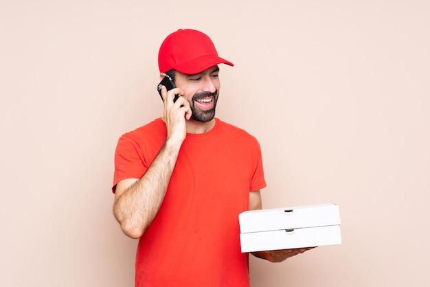 Jovem, segurando uma pizza, mantendo uma conversa com o telefone móvel