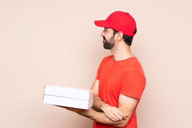Jovem, segurando uma pizza na posição lateral