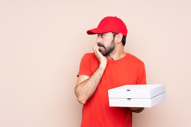 Jovem, segurando uma pizza nervosa e assustada, colocando as mãos na boca