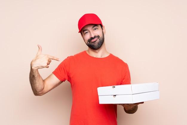 Jovem, segurando uma pizza orgulhoso e satisfeito
