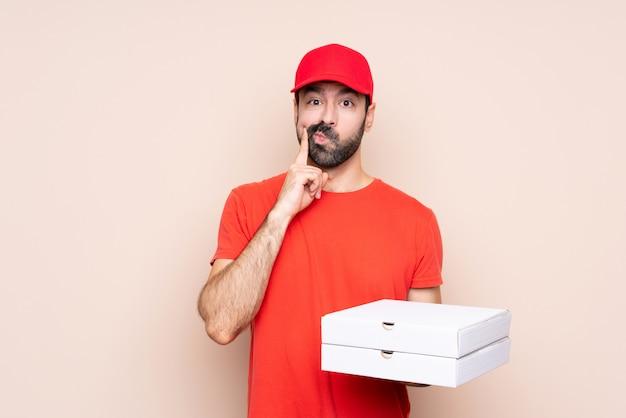 Jovem, segurando uma pizza sobre isolado, olhando de frente