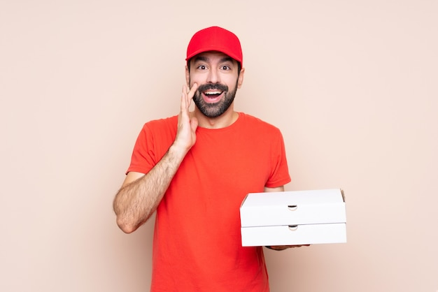 Jovem, segurando uma pizza sobre parede isolada com surpresa e expressão facial chocado