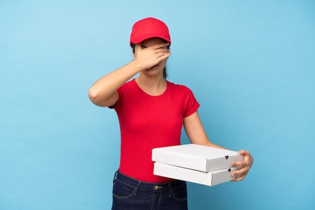 Jovem, segurando uma pizza sobre parede rosa isolada, cobrindo os olhos pelas mãos
