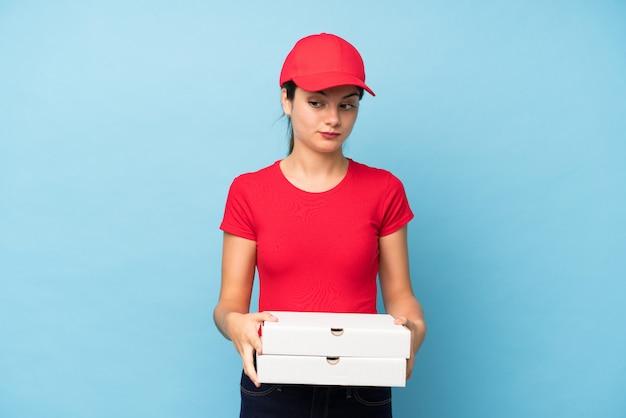 Jovem, segurando uma pizza sobre parede rosa isolada, pensando em uma idéia
