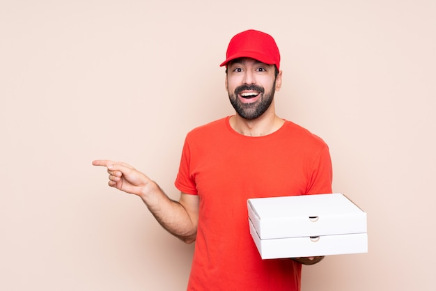 Jovem, segurando uma pizza surpreendeu e apontando o dedo para o lado