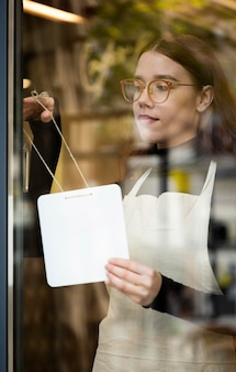 Jovem segurando uma placa de loja