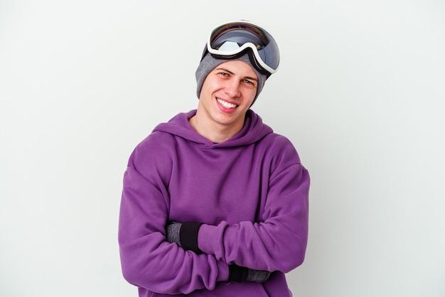 Jovem segurando uma prancha de snowboard isolada na parede branca, rindo e se divertindo.