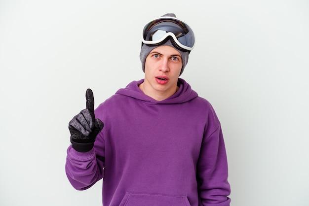 Jovem segurando uma prancha de snowboard isolada na parede branca, tendo uma ideia, o conceito de inspiração.
