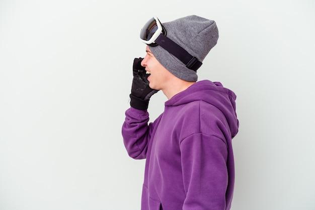 Jovem segurando uma prancha de snowboard isolada no branco gritando e segurando a palma da mão perto da boca aberta.
