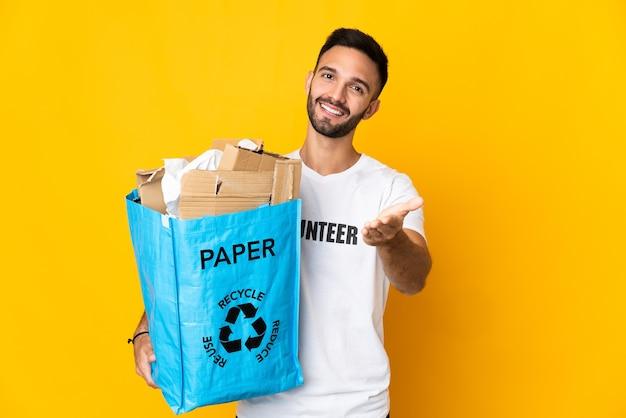Jovem segurando uma sacola cheia de papel para reciclar isolada na parede branca apertando as mãos para fechar um bom negócio