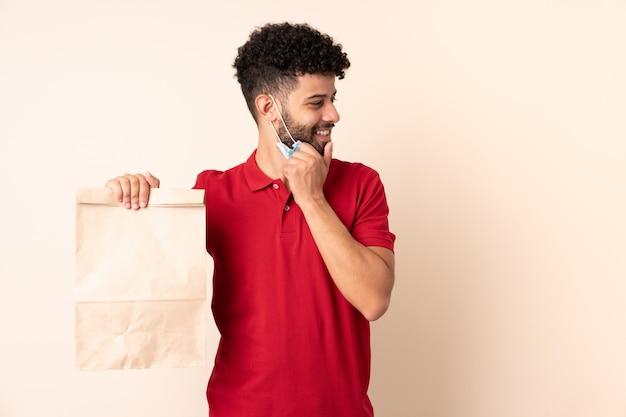 Jovem segurando uma sacola de comida para viagem ___ pensando em uma ideia e olhando para o lado
