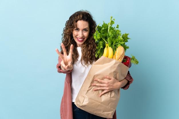 Jovem segurando uma sacola de compras de supermercado
