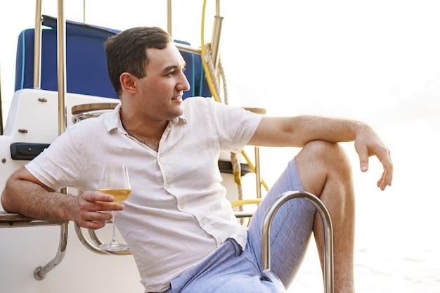 Jovem segurando uma taça de vinho no convés aberto de um barco de cruzeiro