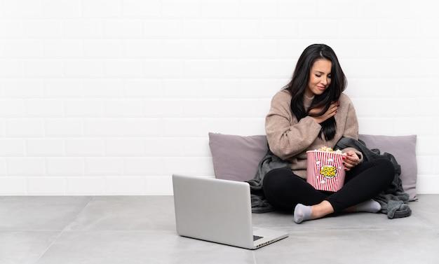 Jovem, segurando uma tigela de pipocas e mostrando um filme em um laptop com uma dor no coração