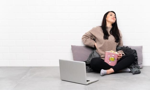 Jovem, segurando uma tigela de pipocas e mostrando um filme em um laptop que sofre de dor nas costas por ter feito um esforço