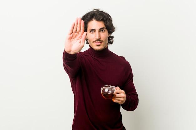 Jovem segurando uma xícara de chá de pé com a mão estendida, mostrando o sinal de pare, impedindo você.