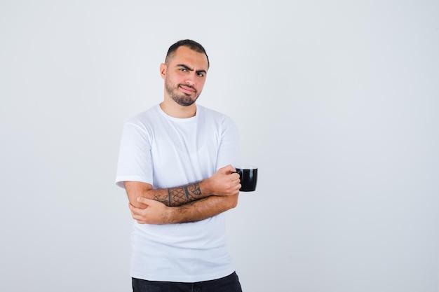 Jovem segurando uma xícara de chá e braços cruzados em uma camiseta branca e calça preta e parecendo feliz