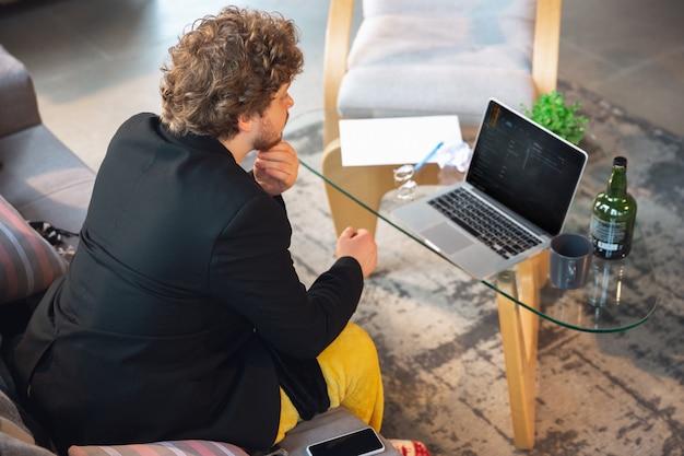Jovem sem calças, mas no casaco, trabalhando em um computador, laptop.