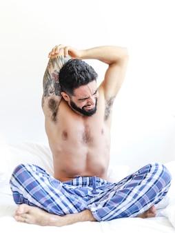 Jovem sem camisa, esticando os braços na cama