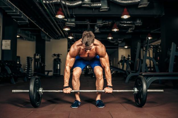 Jovem sem camisa fazendo levantamento terra no ginásio.