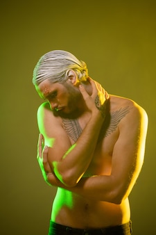 Jovem sem camisa, iluminado por trás, com maquiagem de palco, cabelo branco em penteado preciso e tatuagem no peito e as mãos mantendo a cabeça no ombro direito