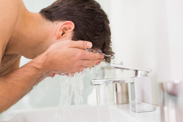 Jovem sem camisa, lavar o rosto no banheiro
