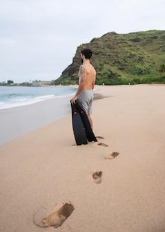 Jovem sem camisa na praia com equipamento de mergulho