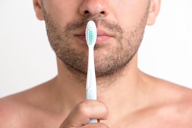 Jovem sem camisa, segurando a escova de dentes na frente de seus lábios