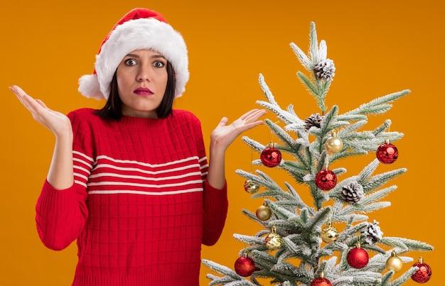 Jovem sem noção com chapéu de papai noel em pé perto da árvore de natal decorada, mostrando as mãos vazias isoladas na parede laranja