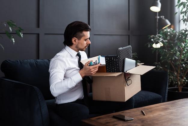Jovem sendo demitido do emprego. empresário e caixa de papelão com seus pertences pessoais de um local de trabalho.
