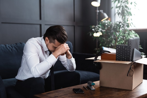 Jovem sendo demitido do emprego. empresário e caixa de papelão com suas coisas pessoais do trabalho.