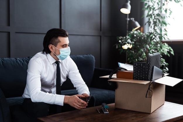 Jovem sendo demitido do emprego por causa de uma pandemia de vírus. empresário e caixa de papelão com suas coisas pessoais do trabalho.