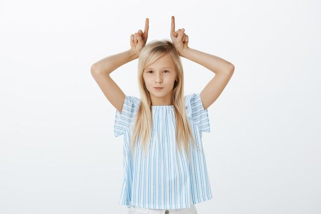 Jovem sendo teimosa, não tendo respeito pelos adultos. retrato de filha fofa confiante indiferente com cabelo loiro, segurando o dedo indicador na cabeça, imitando chifres e sorrindo