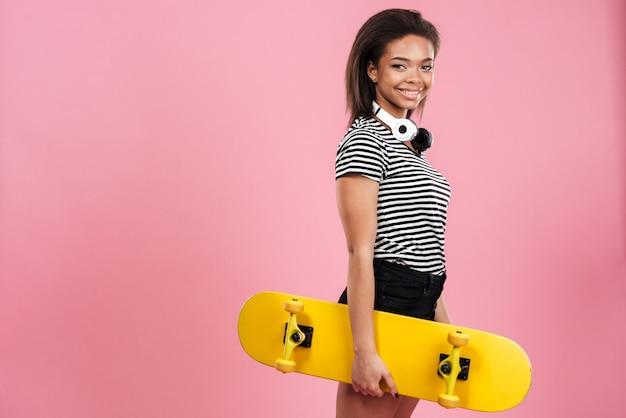 Jovem senhora africana em pé isolado sobre parede rosa