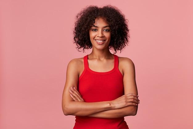 Jovem senhora afro-americana de beleza com cabelo escuro encaracolado, vestindo camiseta vermelha, sorrindo e olhando com os braços cruzados isolados.