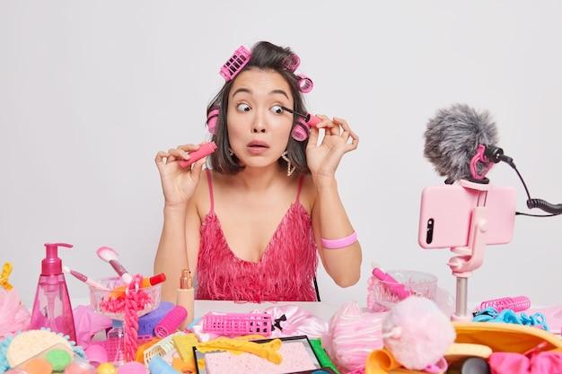 Jovem senhora asiática aplica rímel, apresenta novos produtos de beleza, grava vídeos de transmissão ao vivo sentada em uma mesa bagunçada usa rolos de cabelo vestido rosa isolado no branco