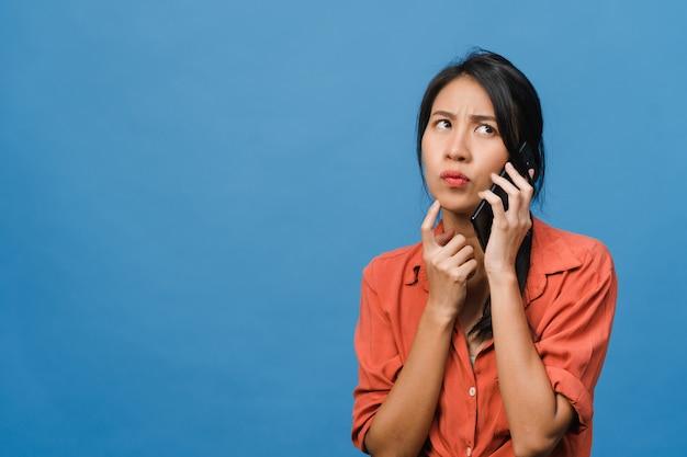 Jovem senhora asiática fala por telefone com expressão negativa, gritando animado, chora com raiva emocional em um pano casual e fica isolado na parede azul com espaço de cópia em branco. conceito de expressão facial.