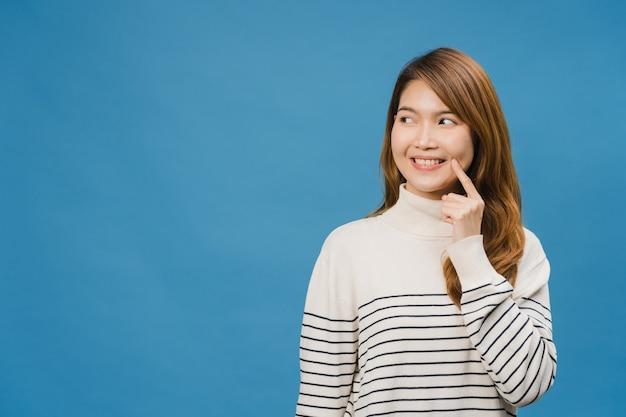 Jovem senhora asiática mostrando sorriso, expressão positiva, vestida com roupas casuais e se sentindo divertida isolada na parede azul