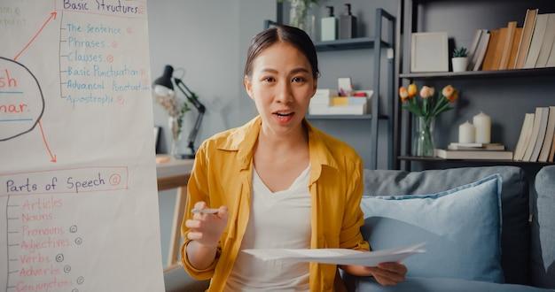 Jovem senhora asiática professora de inglês em videoconferência olhando para câmera falando por webcam, aprendendo, ensinando em chat online em casa