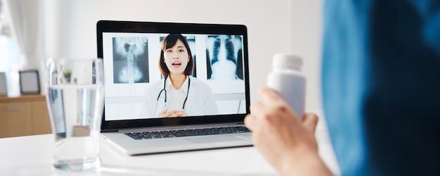 Jovem senhora asiática usando computador laptop fala sobre uma doença em videoconferência com consulta on-line do médico sênior na sala de estar em casa.