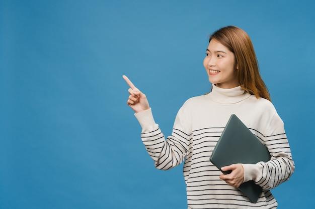 Jovem senhora asiática usando laptop com expressão positiva, sorri amplamente, vestida com roupas casuais, sentindo felicidade e parada isolada na parede azul